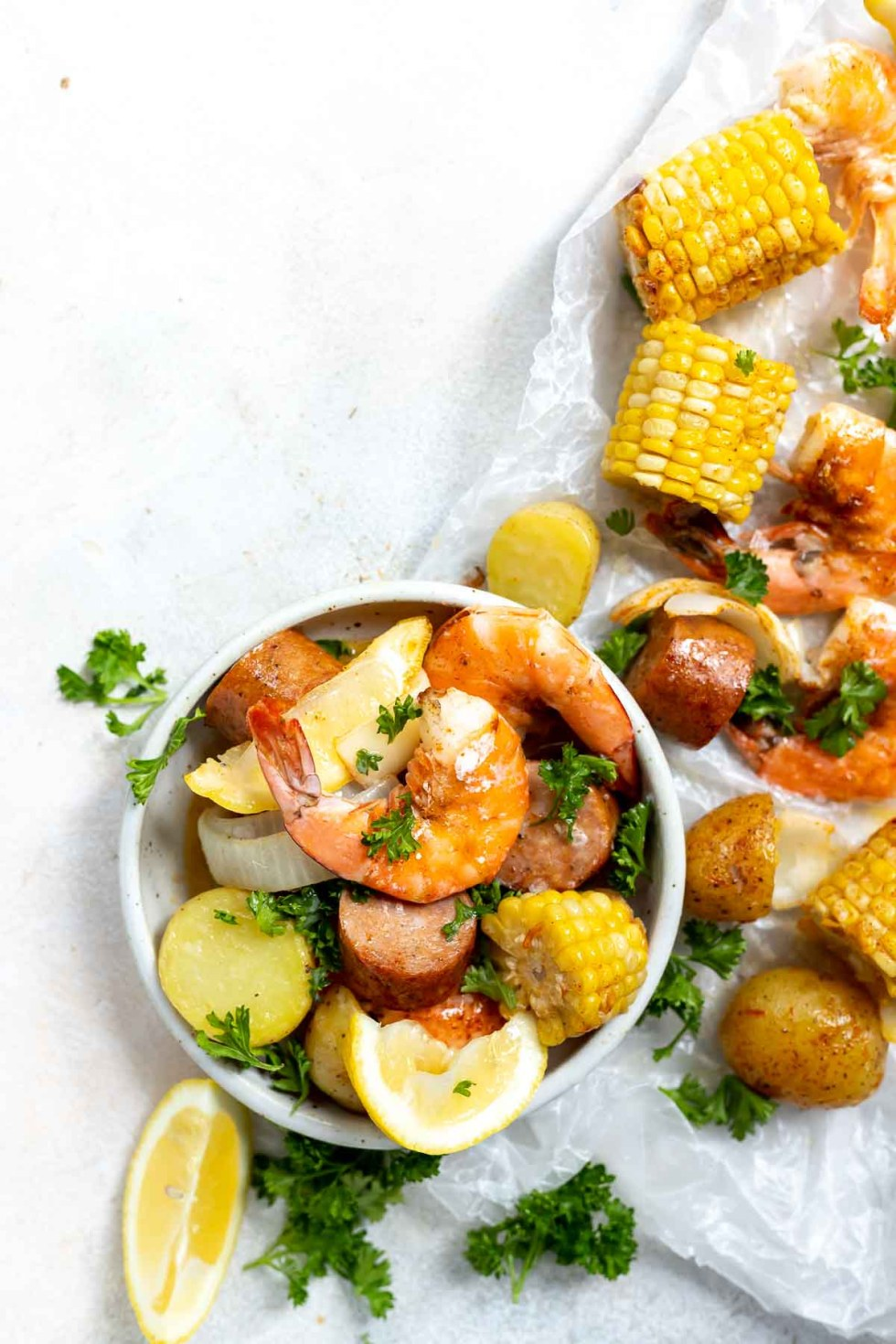 sheet pan shrimp boil ingredients served in white bowl with white background