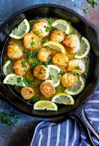 seared scallops with lemon slices in cast iron pan