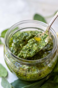basil spinach pesto in glass jar with silver spoon