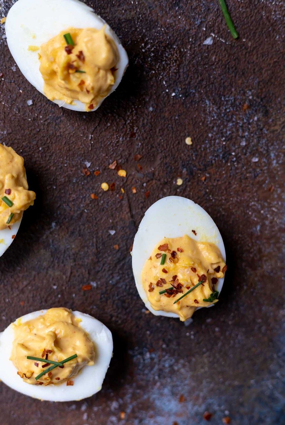 spicy deviled eggs topped with chili flakes and chives