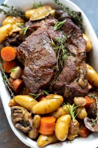 pot roast, potatoes, carrots and mushrooms ready to be served