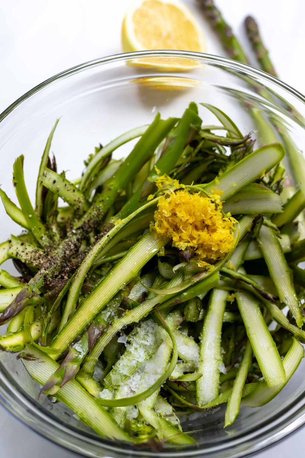 shaved asparagus, lemon zest, salt and pepper in glass bowl