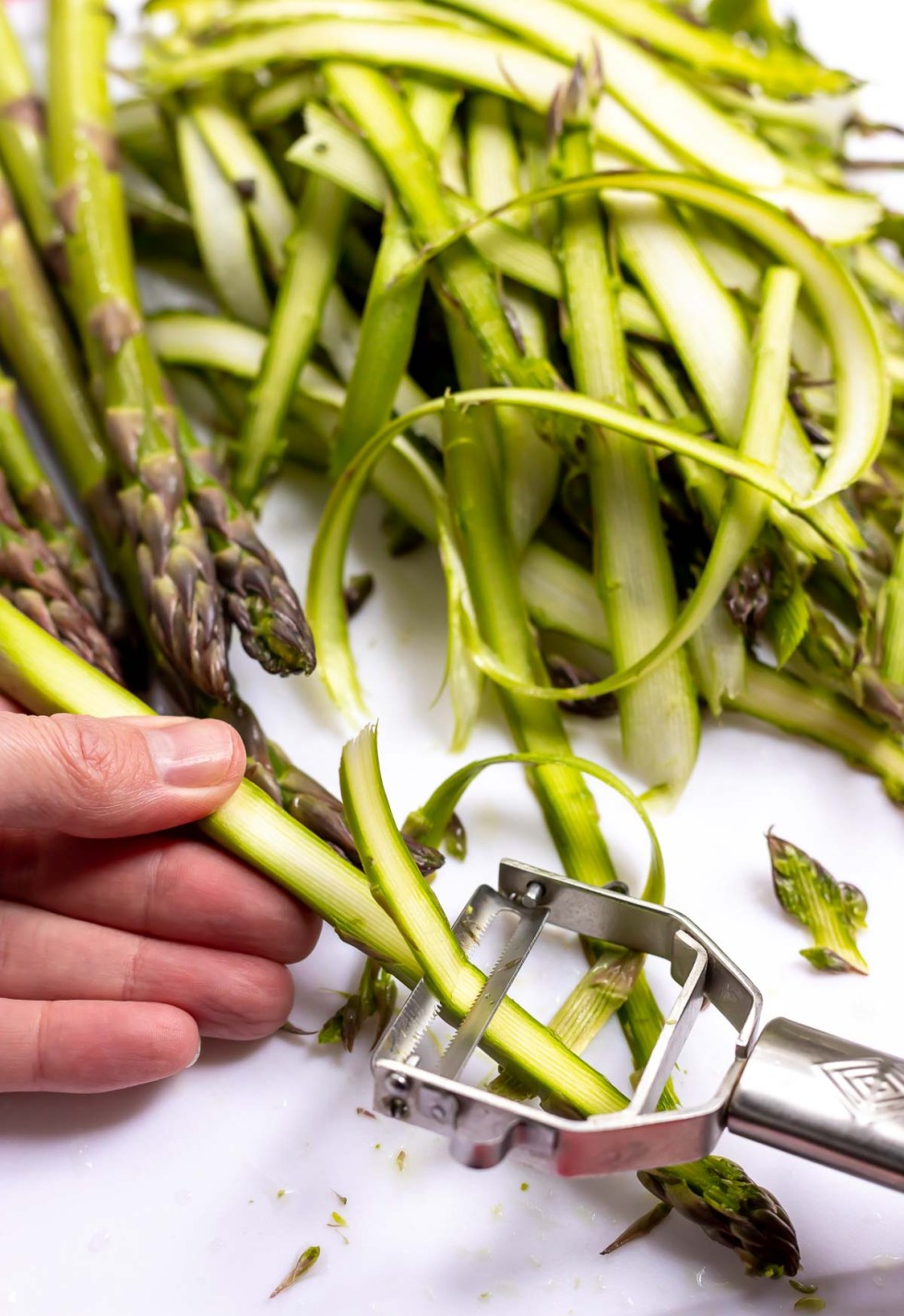 asparagus spears being shaved with vegetable peeler