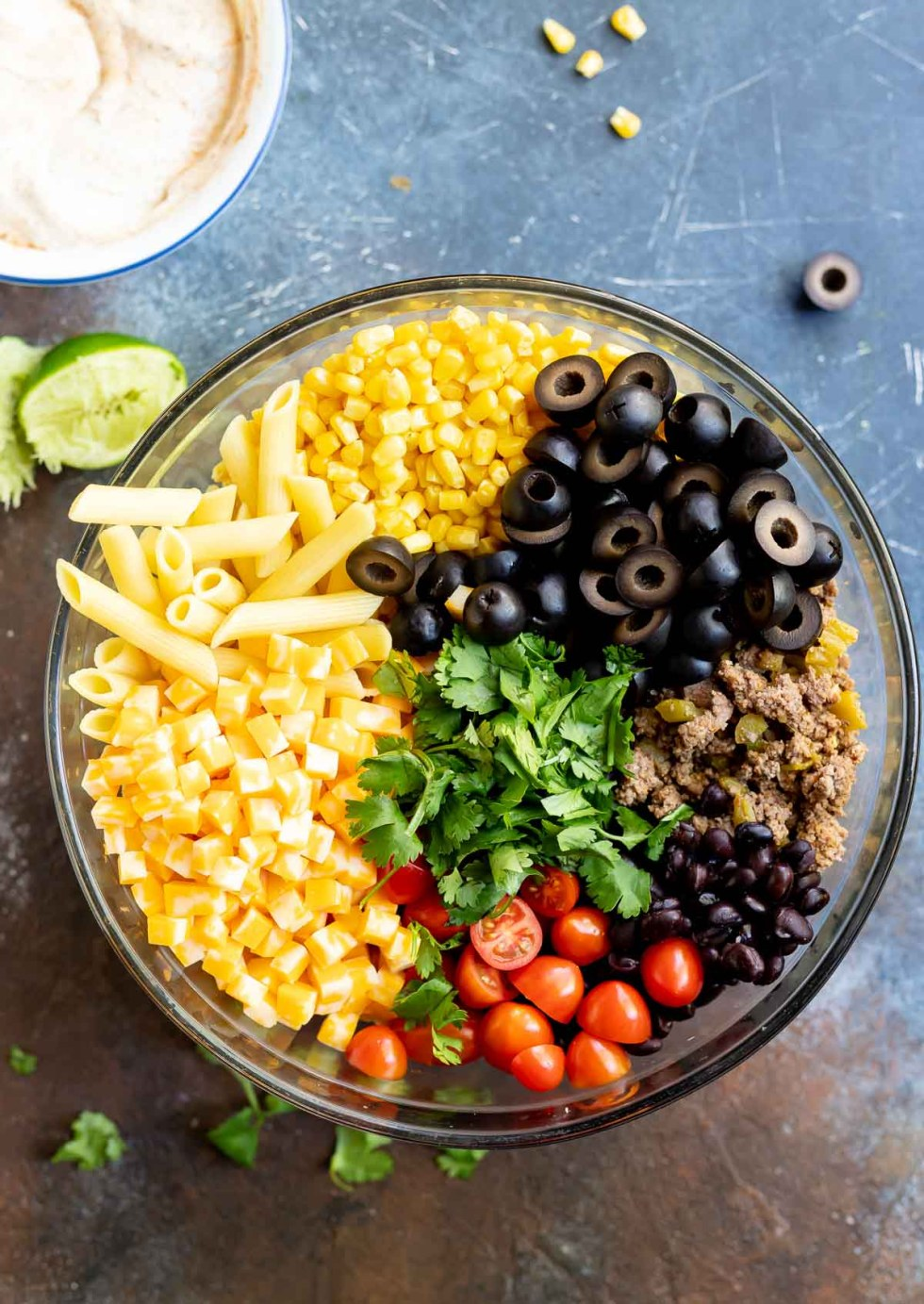 ingredients for taco pasta salad in glass bowl