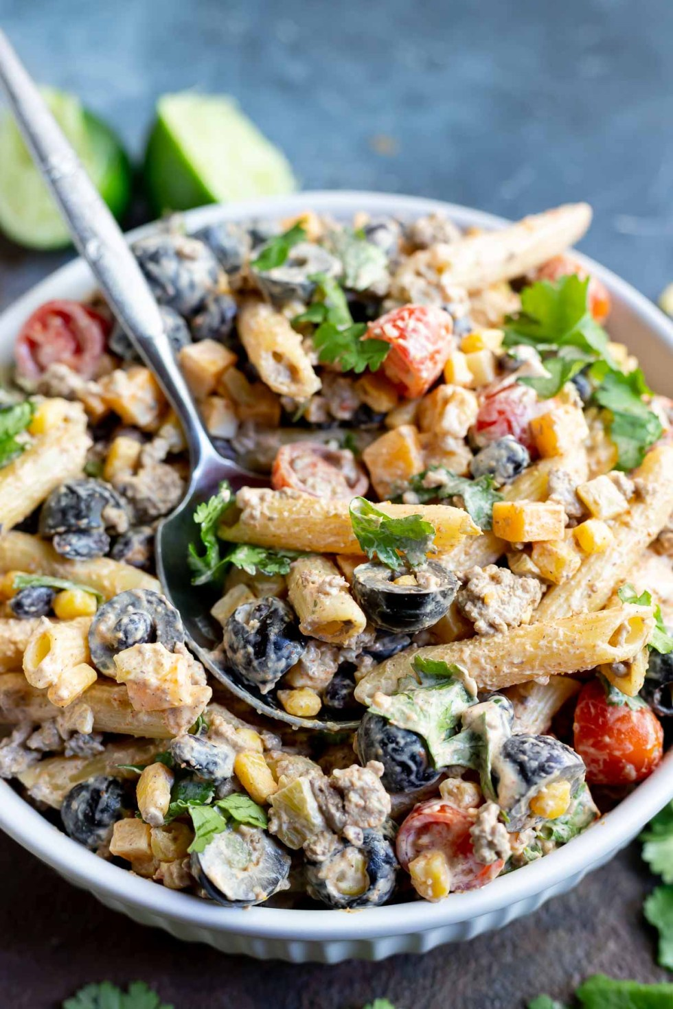 pasta salad loaded with taco ingredients in a white bowl
