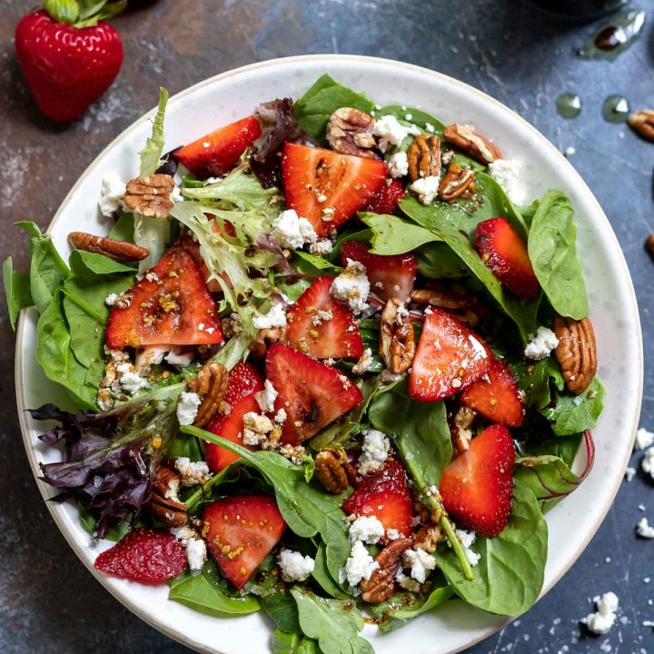 spinach and strawberry salad in white bowl with strawberries on the side