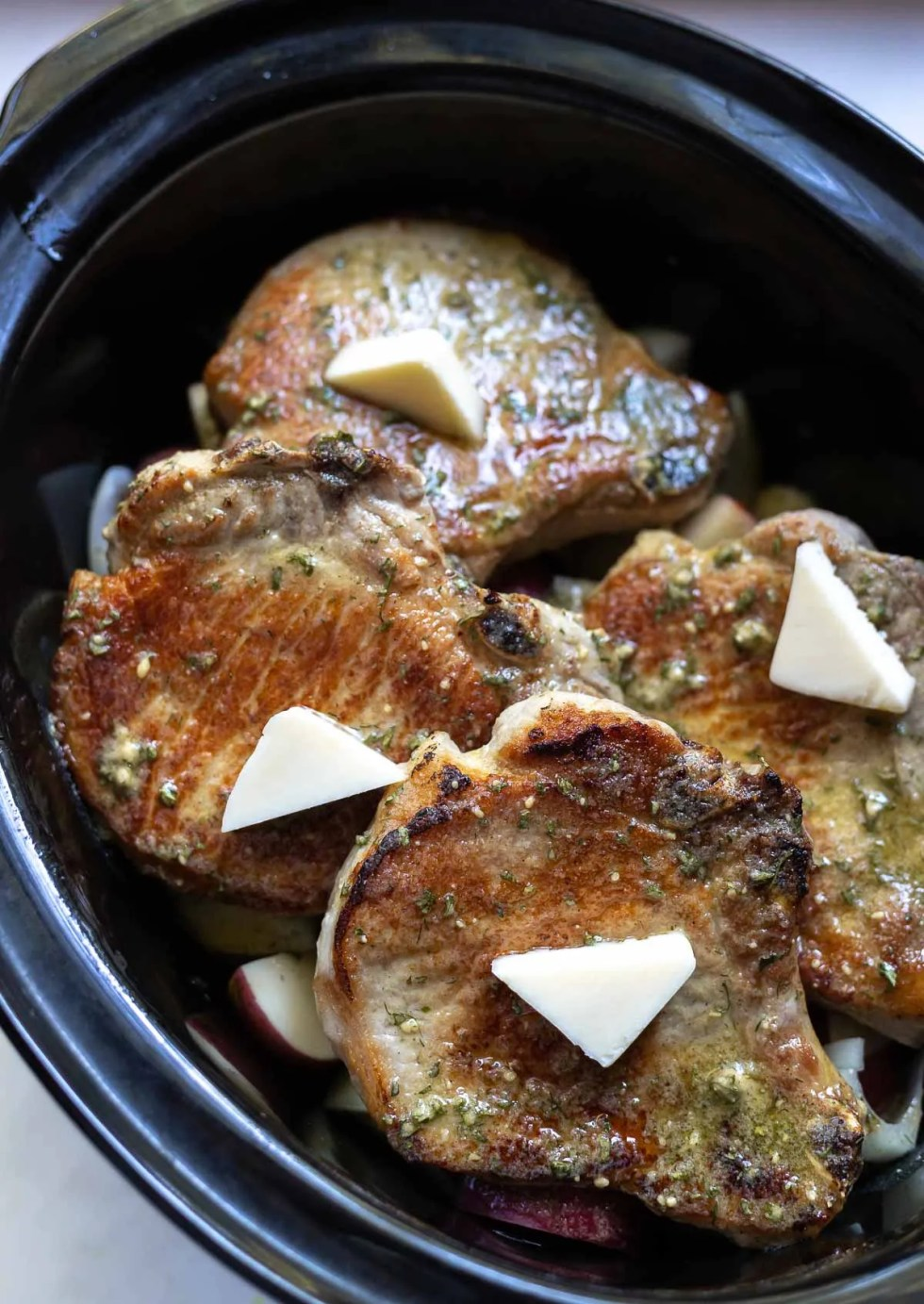 seared pork chops topped with butter in slow cooker