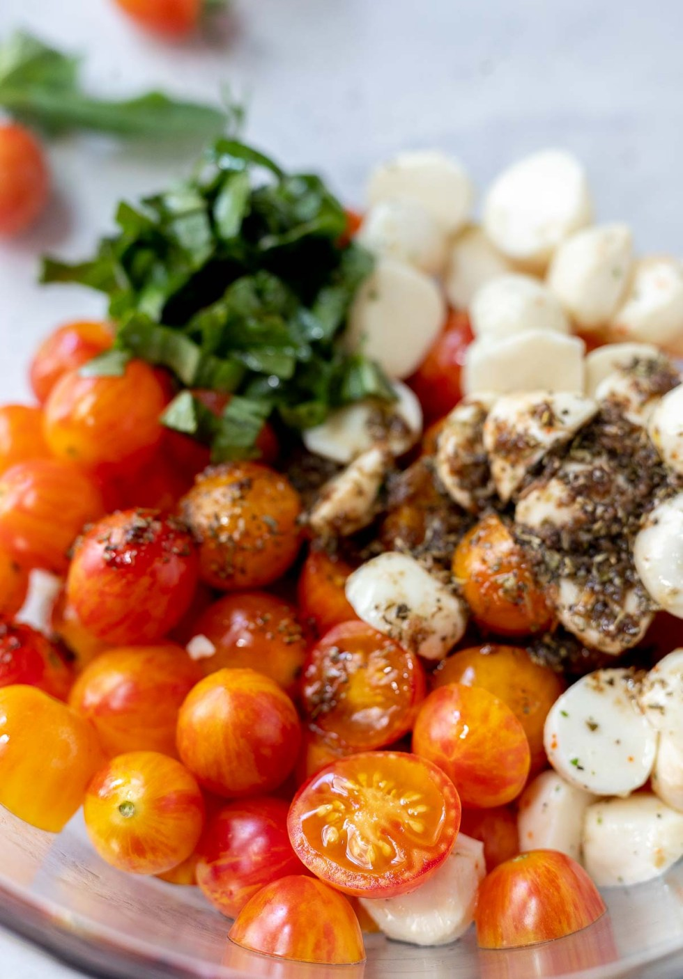 caprese salad ingredients including dressing in clear glass bowl