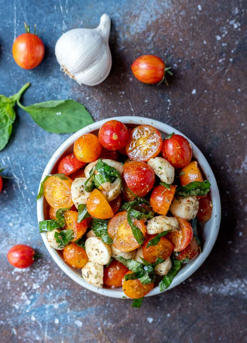 caprese salad in white bowl next to tomatoes basil and garlic