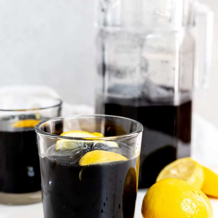 black lemonade in clear glasses and pitcher with lemons on the side