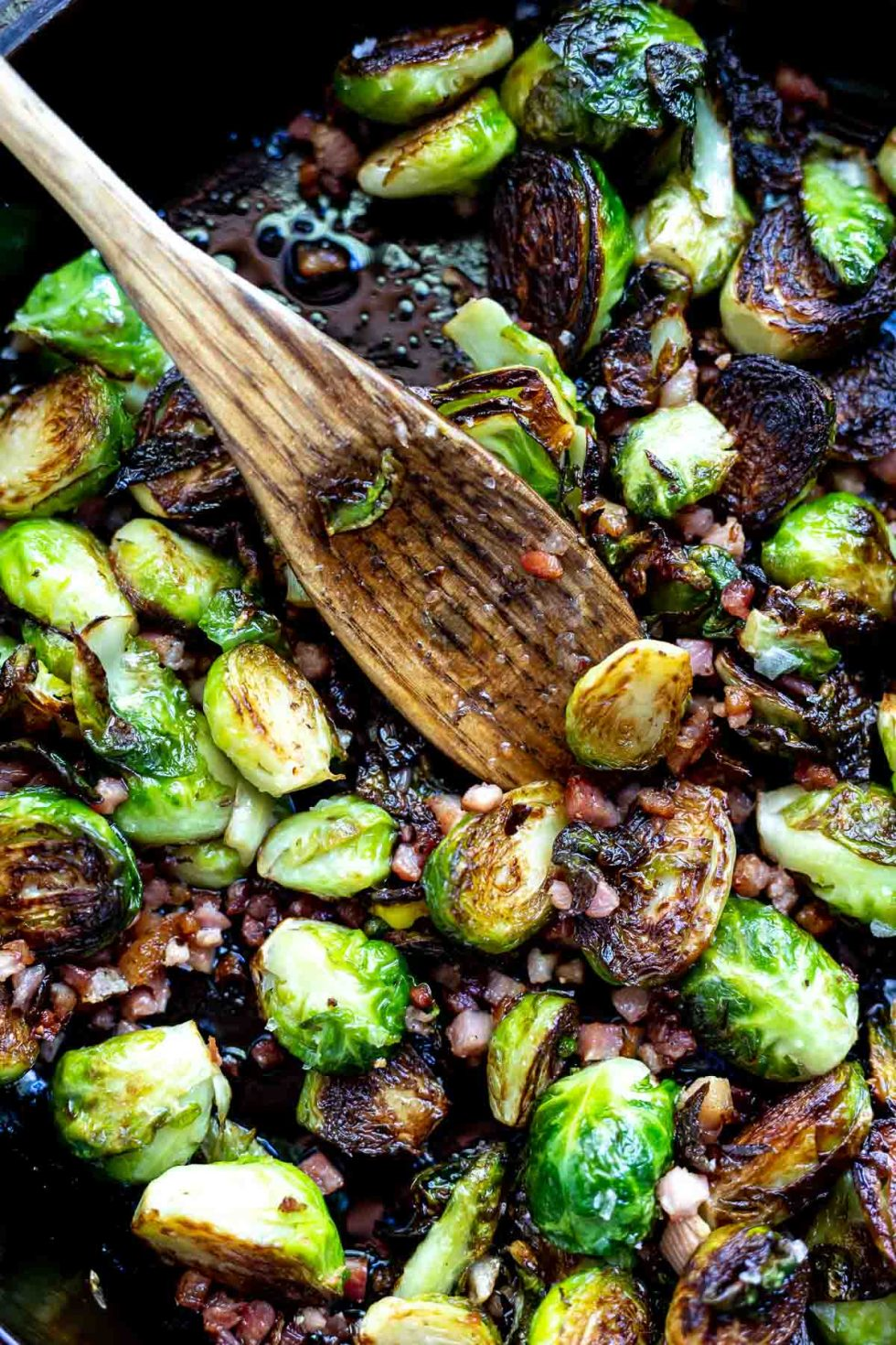 pancetta and brussels sprouts in pan with wooden spoon