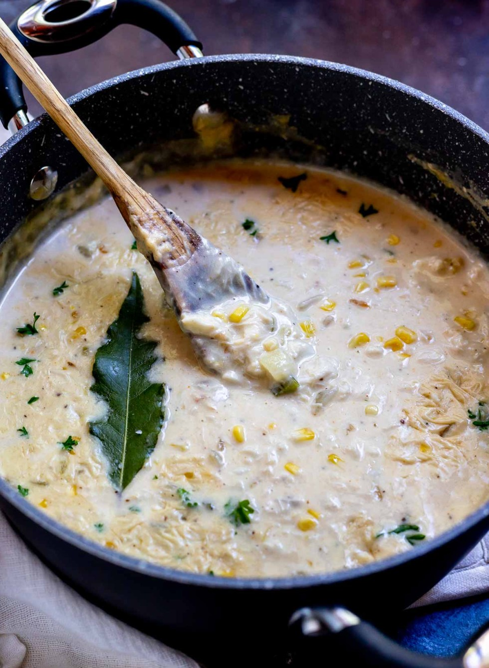 crab chowder in pot with wooden spoon