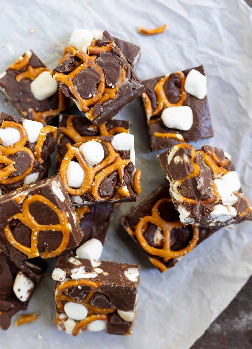 cut chocolate pretzel fudge squares on parchment paper