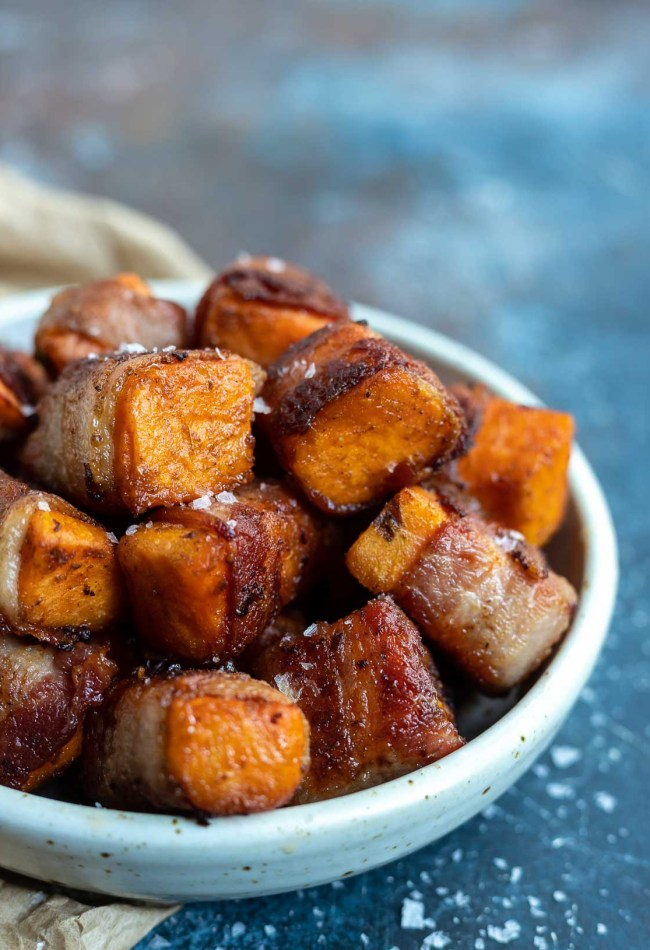 roasted sweet potatoes wrapped in bacon in white dish