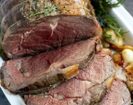 prime rib roast sliced and served on a white platter