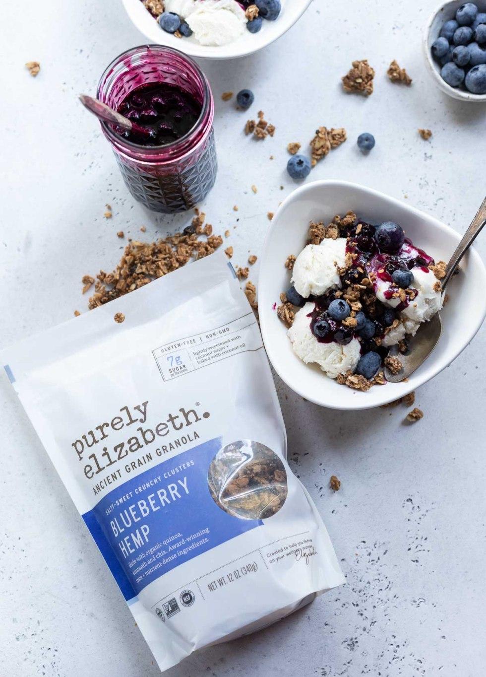 ice cream parfait next to bag of granola and jar of blueberry sauce
