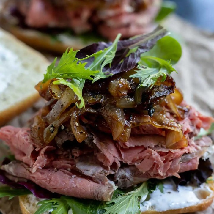 open faced sandwich with prime rib, caramelized onions and greens