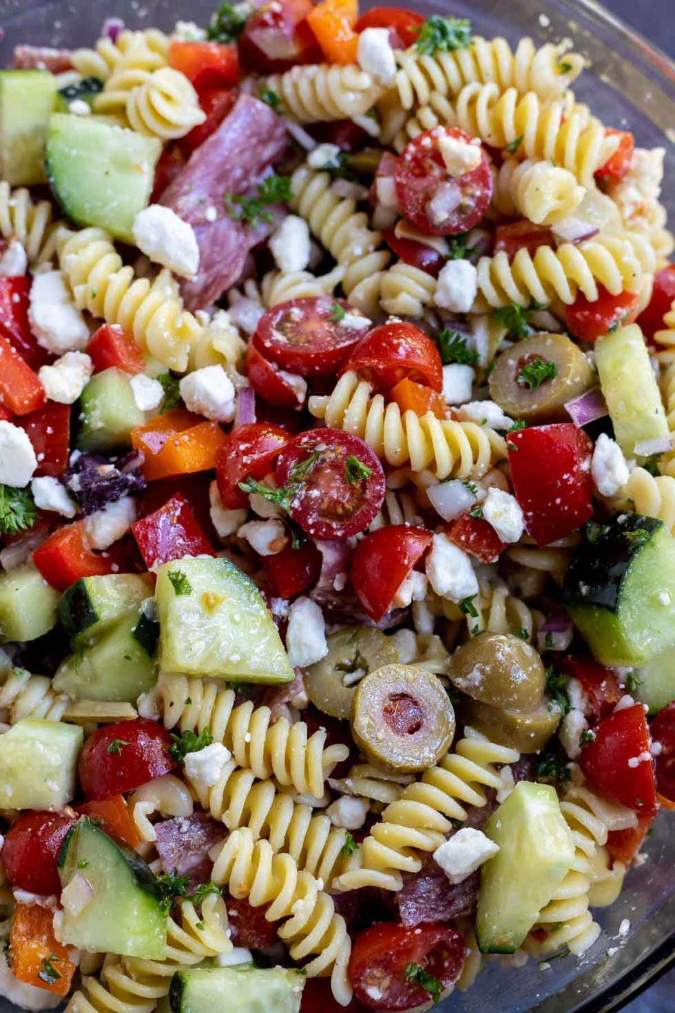pasta, tomatoes, olives, cucumber, salami and crumbles cheese