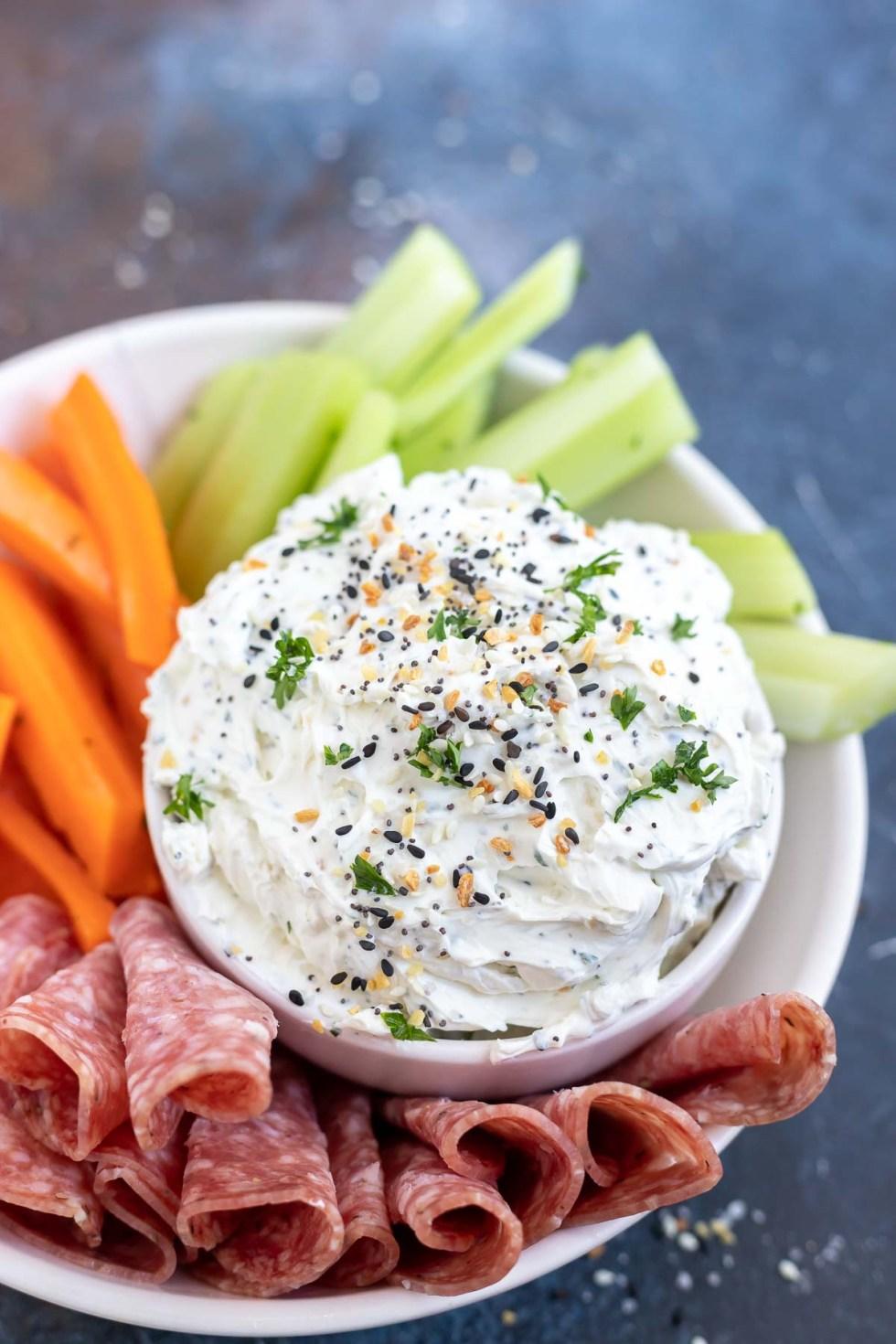 prepared dip in white bowl next to salami and veggies