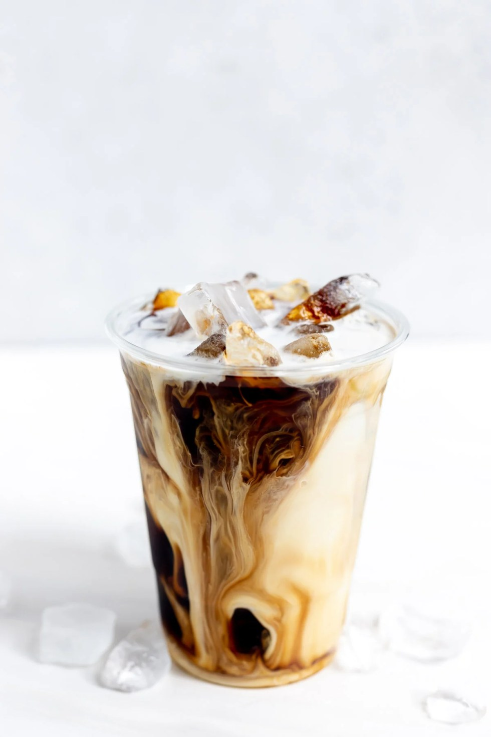 creamy coffee and ice in clear plastic cup