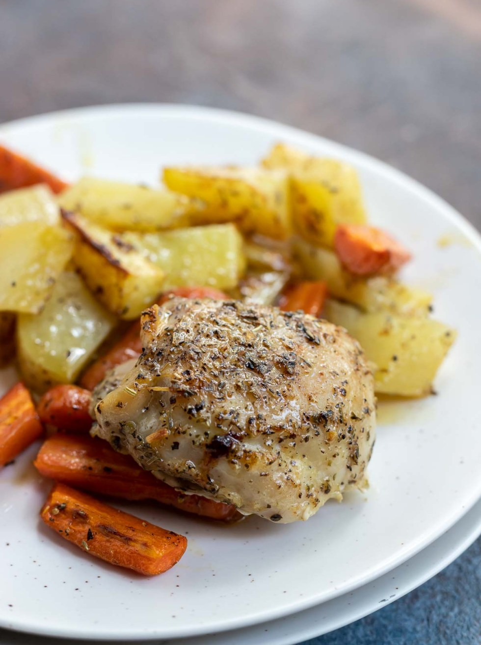 roasted chicken thigh, carrots and potatoes served on white plate