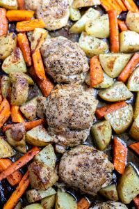 baked chicken thighs, carrots and potatoes on rimmed sheet pan
