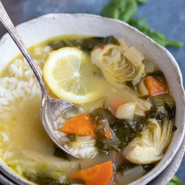 vegetable chicken soup in white bowl with soup spoon