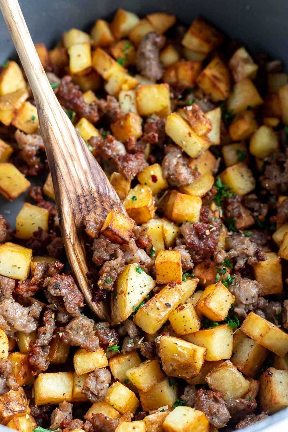 fried potatoes and sausage hash in pot with wooden spoon