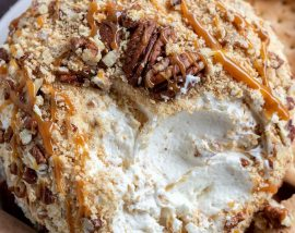 cream cheese ball covered with graham cracker crumbs, chopped pecans and caramel