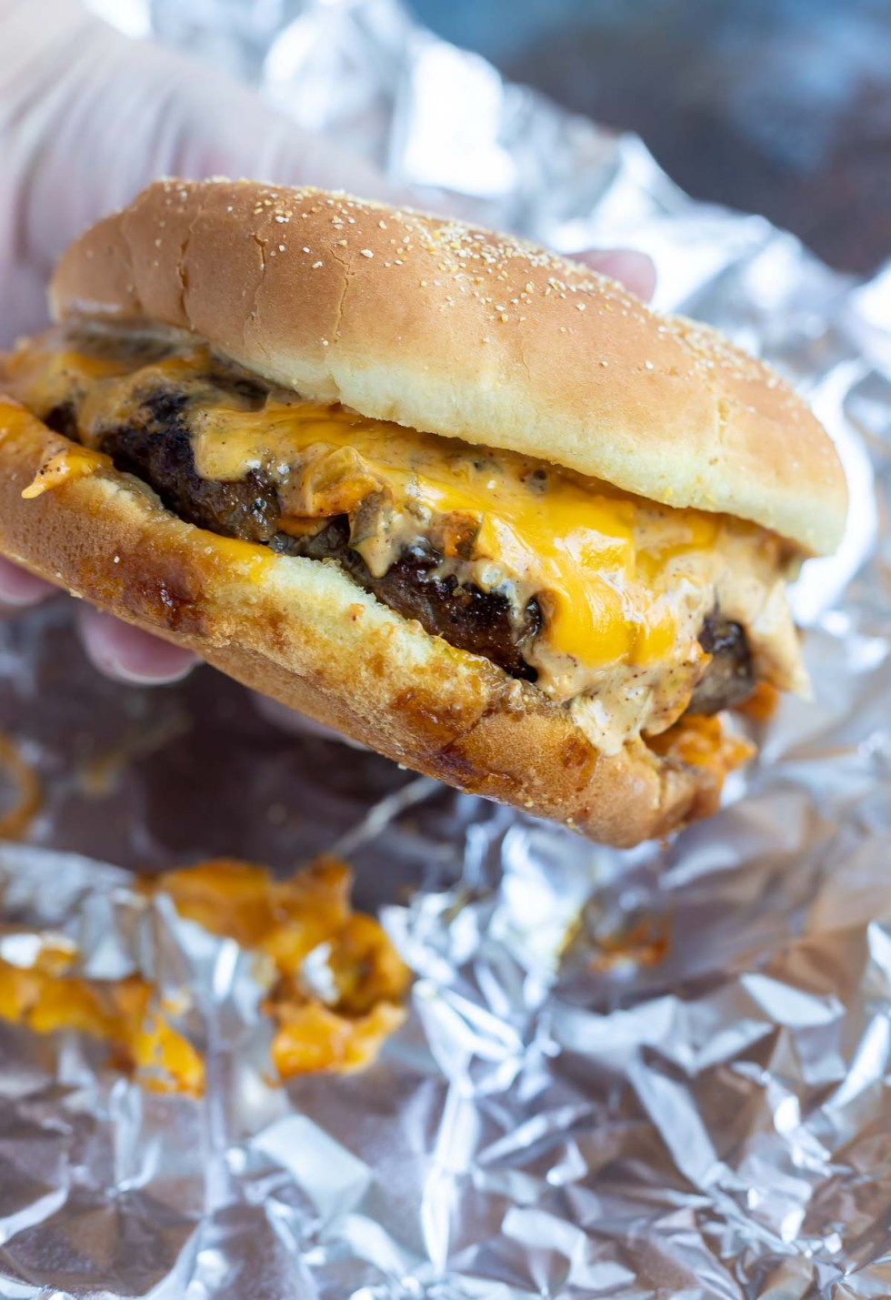 hand holding messy cheeseburger with melted cheese and sauce