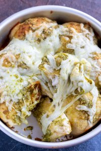 baked rolls topped with melted cheese and pesto
