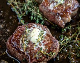 two butter herb topped filet mignon in cast iron pan