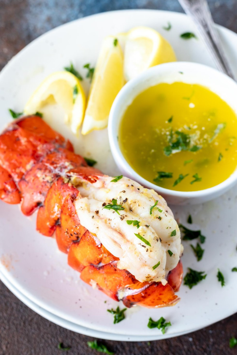 cooked lobster tail and melted butter served on white plate