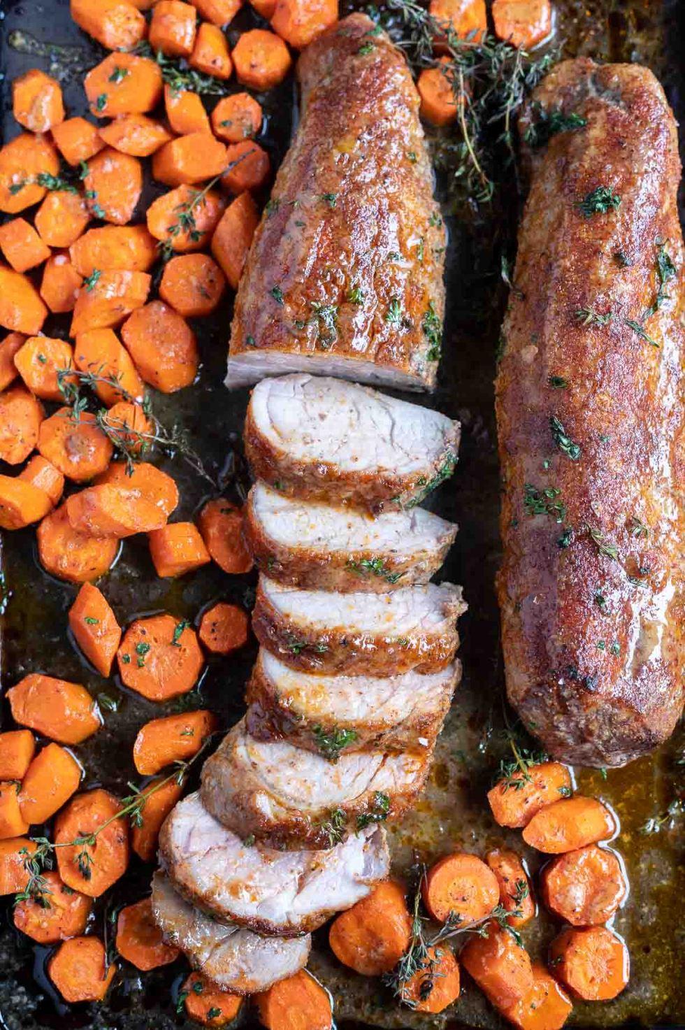partially sliced pork tenderloin and carrots on sheet pan