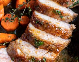 sliced cooked pork tenderloin and carrots on sheet pan