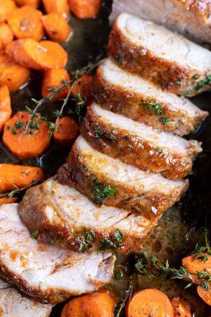 sliced cooked pork tenderloin and carrots on sheet pan