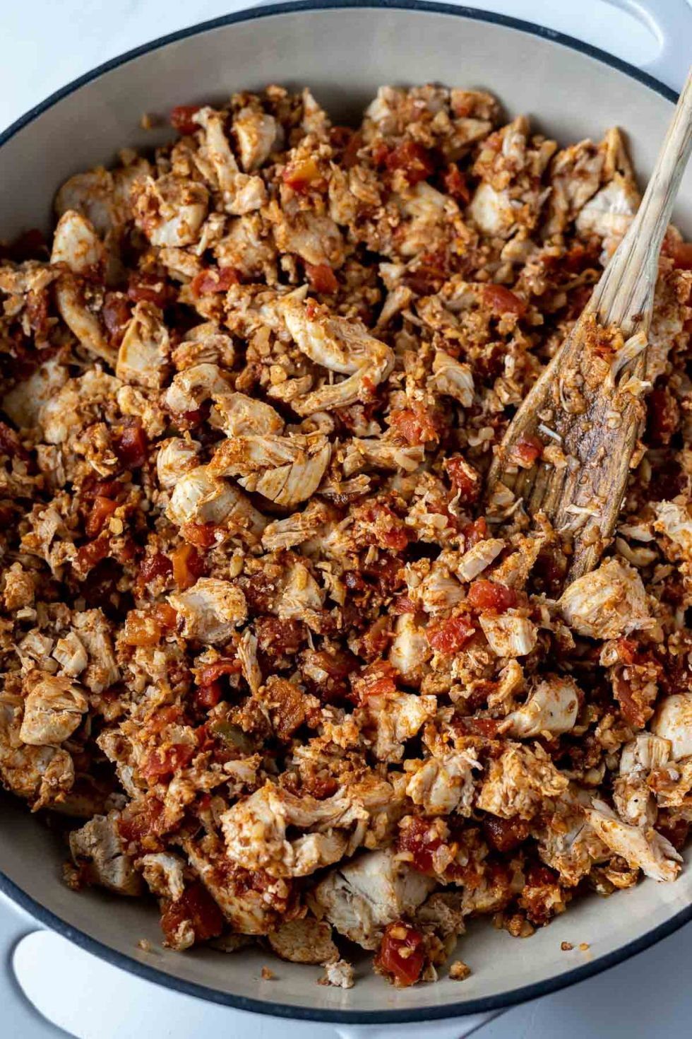 chicken, tomatoes and seasoning in pan with wooden spoon