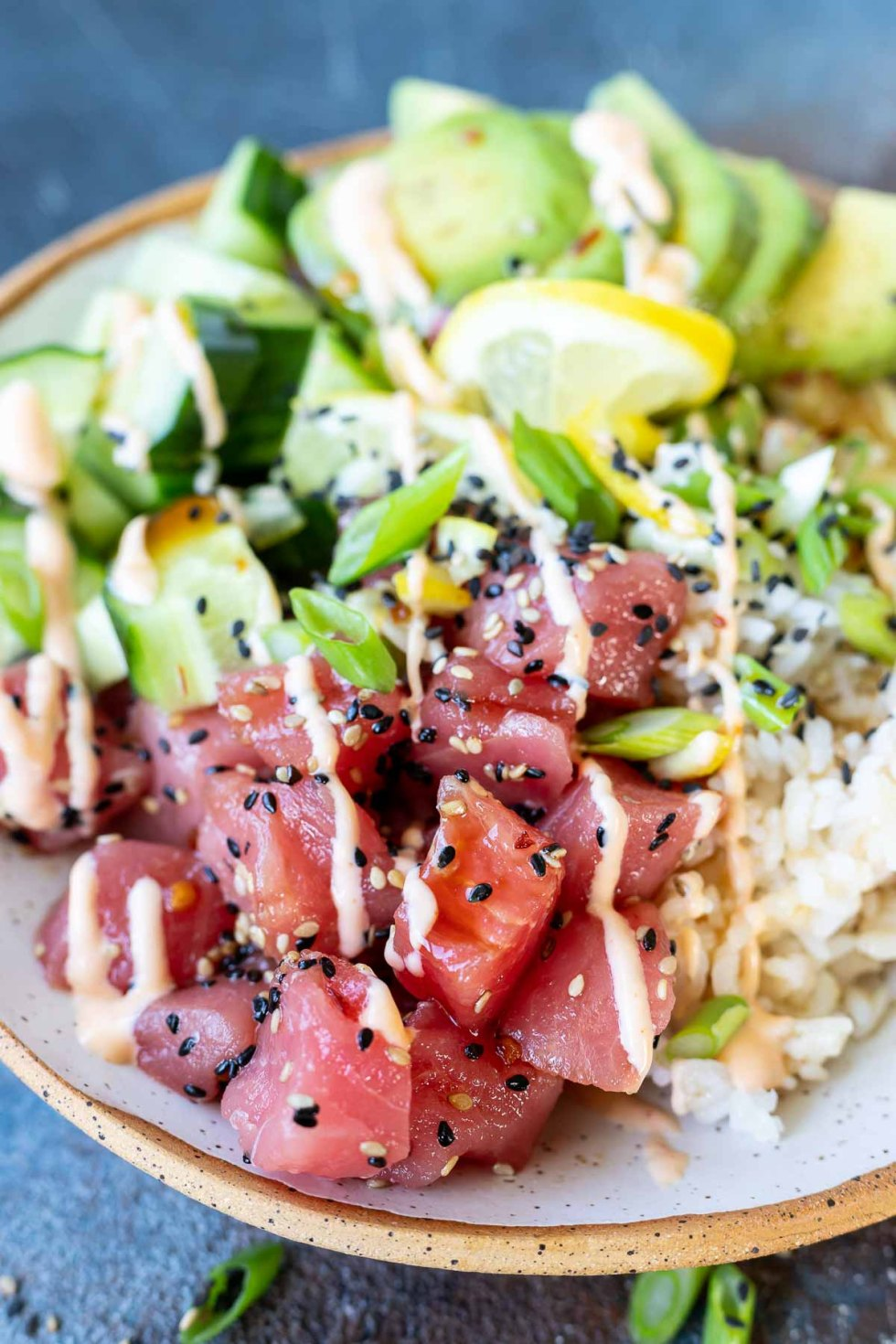 raw tuna, rice, cucumbers and avocado topped with sauce