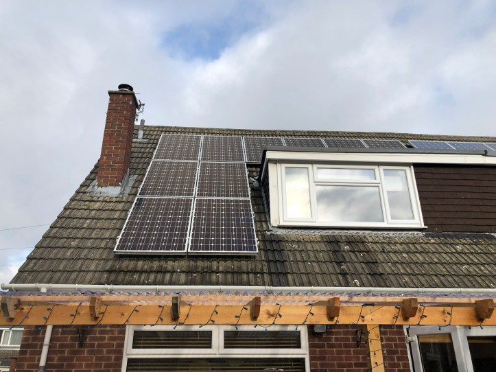 How we reduce our bills using renewable energy - photo of solar panels on our residental home roof with sky and chimney.jpg