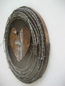 Reclaimed wood with barbed wire, tin roofing, and a found locker plate.