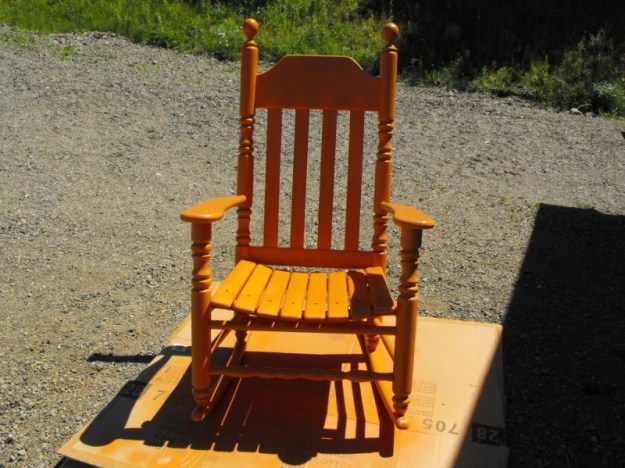 Spray painting a rocking chair.