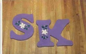 Scroll sawn letters S and K.