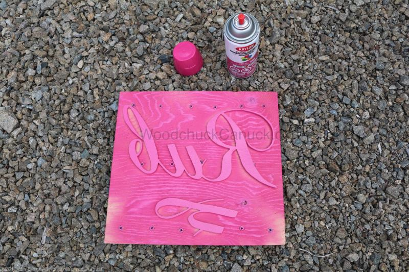 Spray painting a name sign.