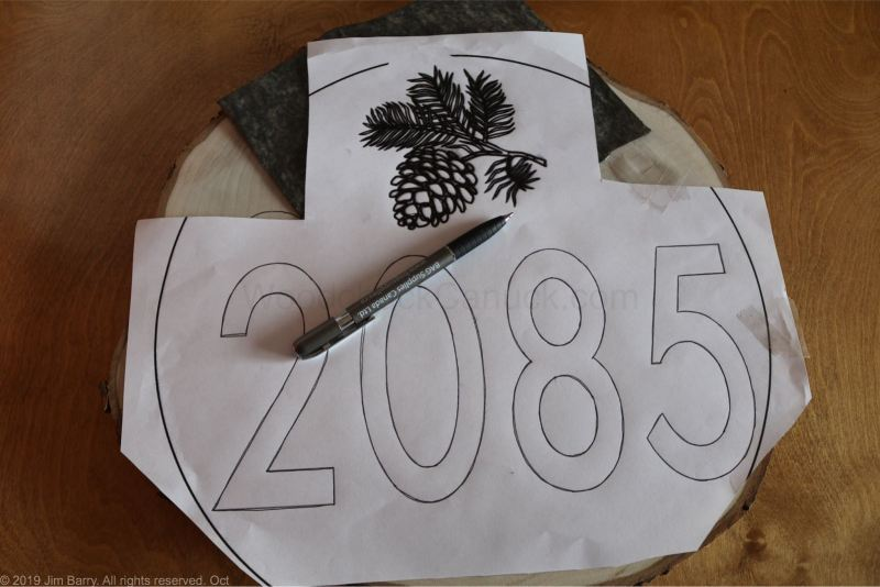 House numbers sign on round wood slice.