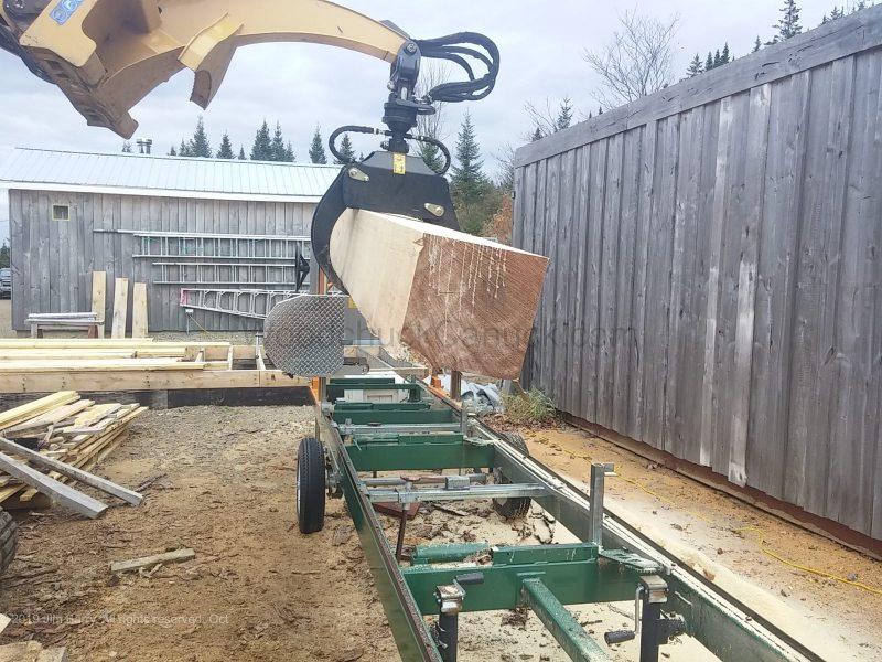 Sawmilling large pine logs in Nova Scotia.