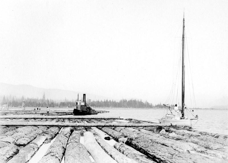 1918 Tugboat and sailboat near log boom.
