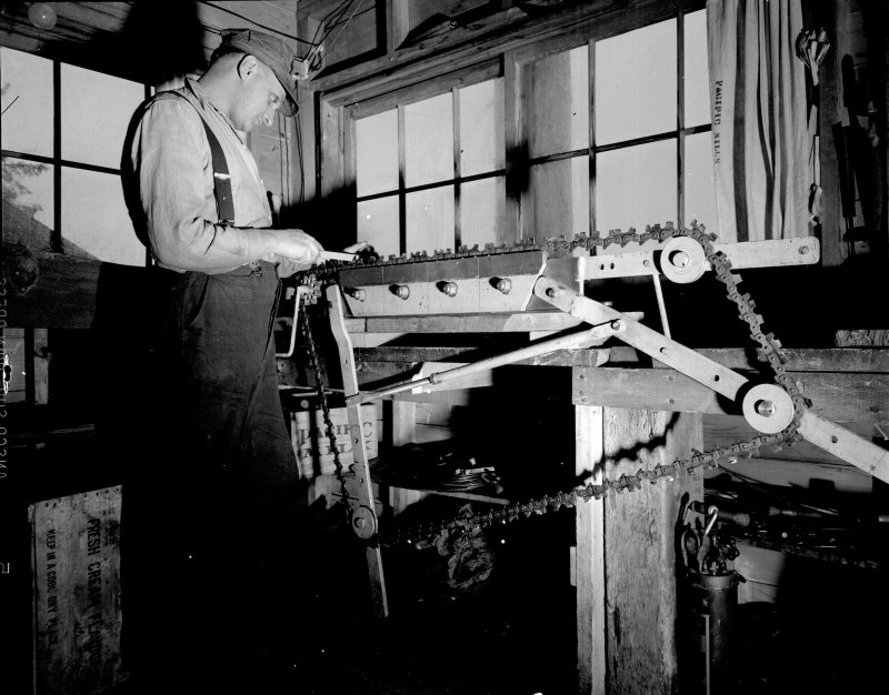 1945 A Man inspecting saw chain