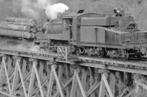 1940-1948 Train pulling a load of logs over a trestle bridge.