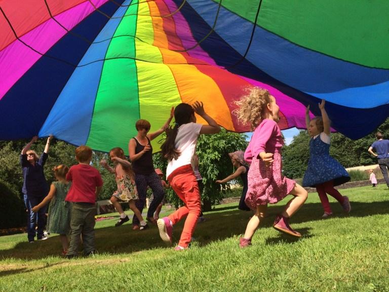 Children running under a rainbow coloured parachute