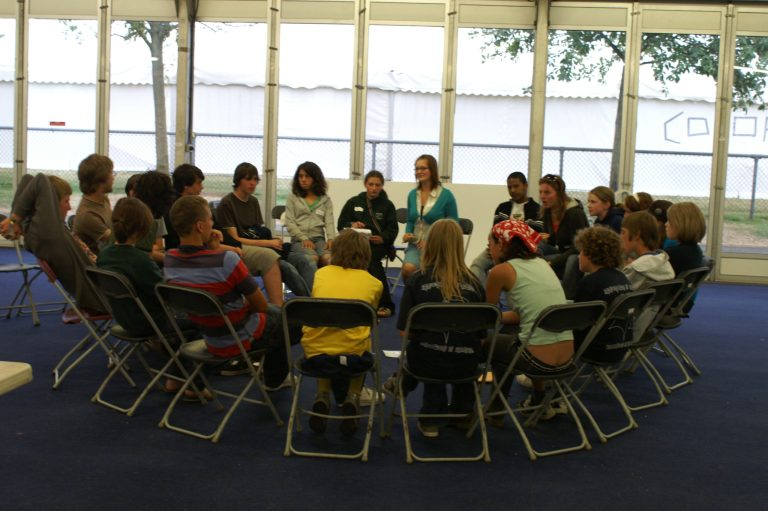 a group of teenagers sitting in a circle having a discussion